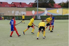Trójka chłopców w żółtych koszulkach biegnąca za piłką, po obu stronach dwóch chłopców w niebieskich koszulkach