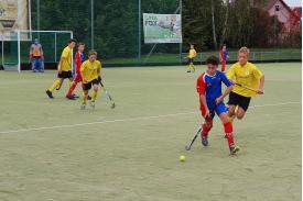 Chłopiec w niebieskiej koszulce z piłką a za nim biegnie chłopiec z przeciwnej drużyny
