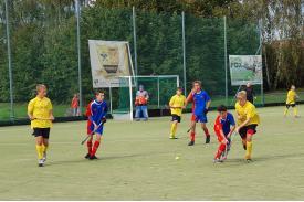 Czworo chłopców w żółtych koszulkach wraz z trójką w niebieskich koszulkach oraz bramkarz w niebieskim kasku