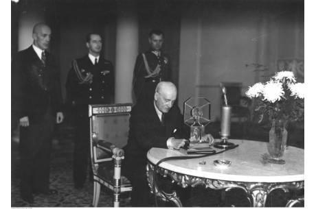 Ignacy Mościcki podczas wygłaszania przemówienia radiowego. Widoczni m.in. kapitan Józef Hartman (stoi, z prawej), kapitan Stefan Kryński (stoi, w środku). Źródło: NAC