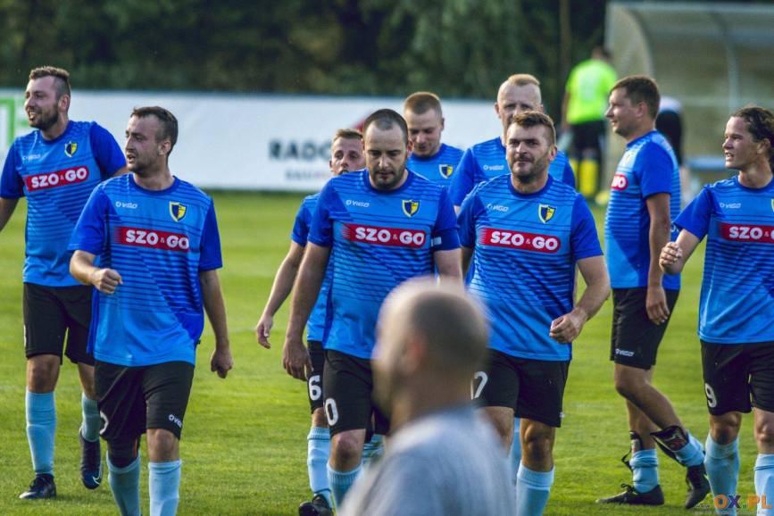 Piłkarze w niebieskich koszulkach i czarnych spodenkach